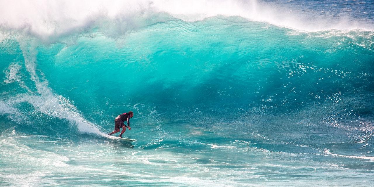 Surfer surfer på kæmpe bølge