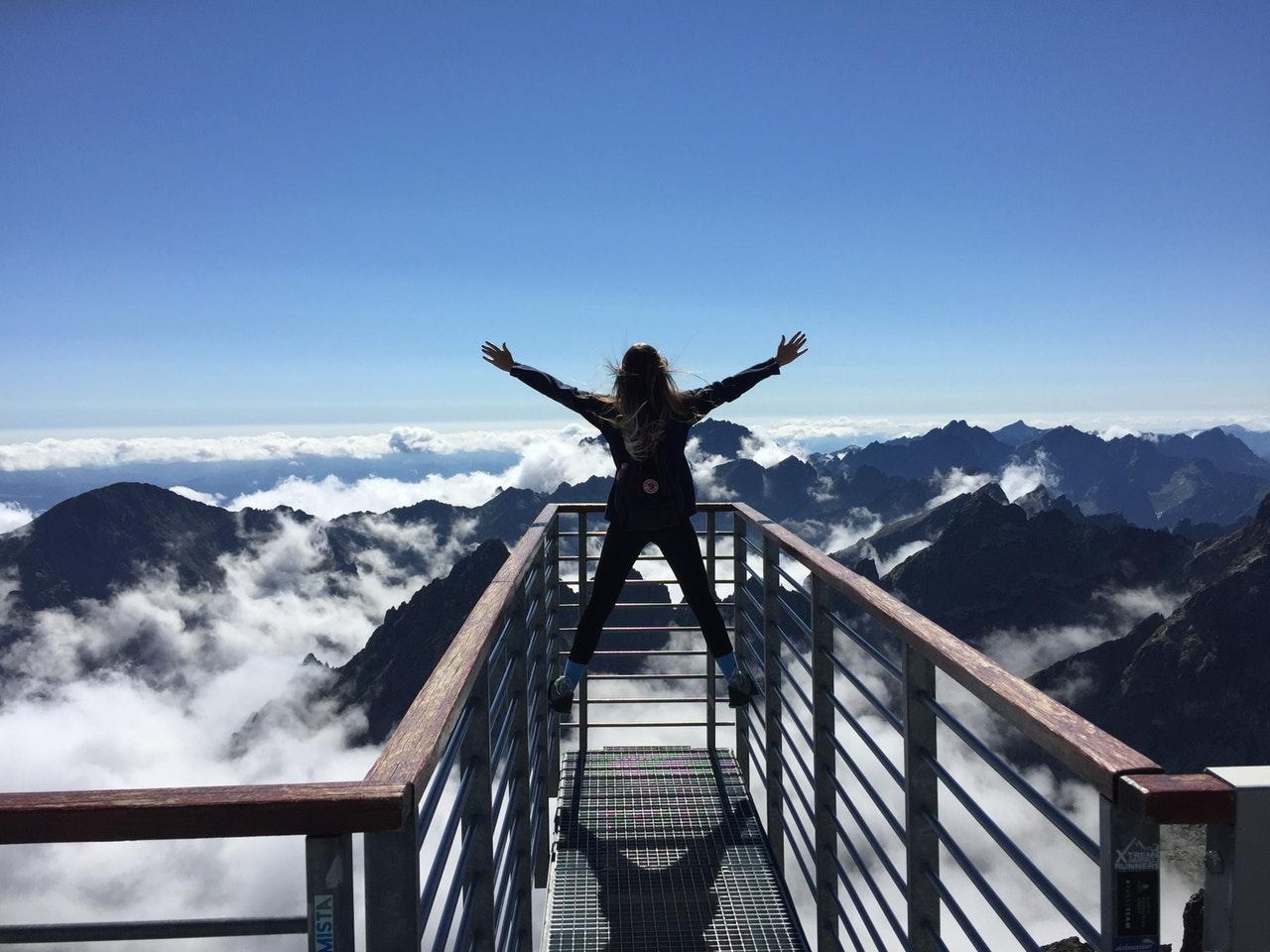 Person står på toppen af bjerg med armene spredt