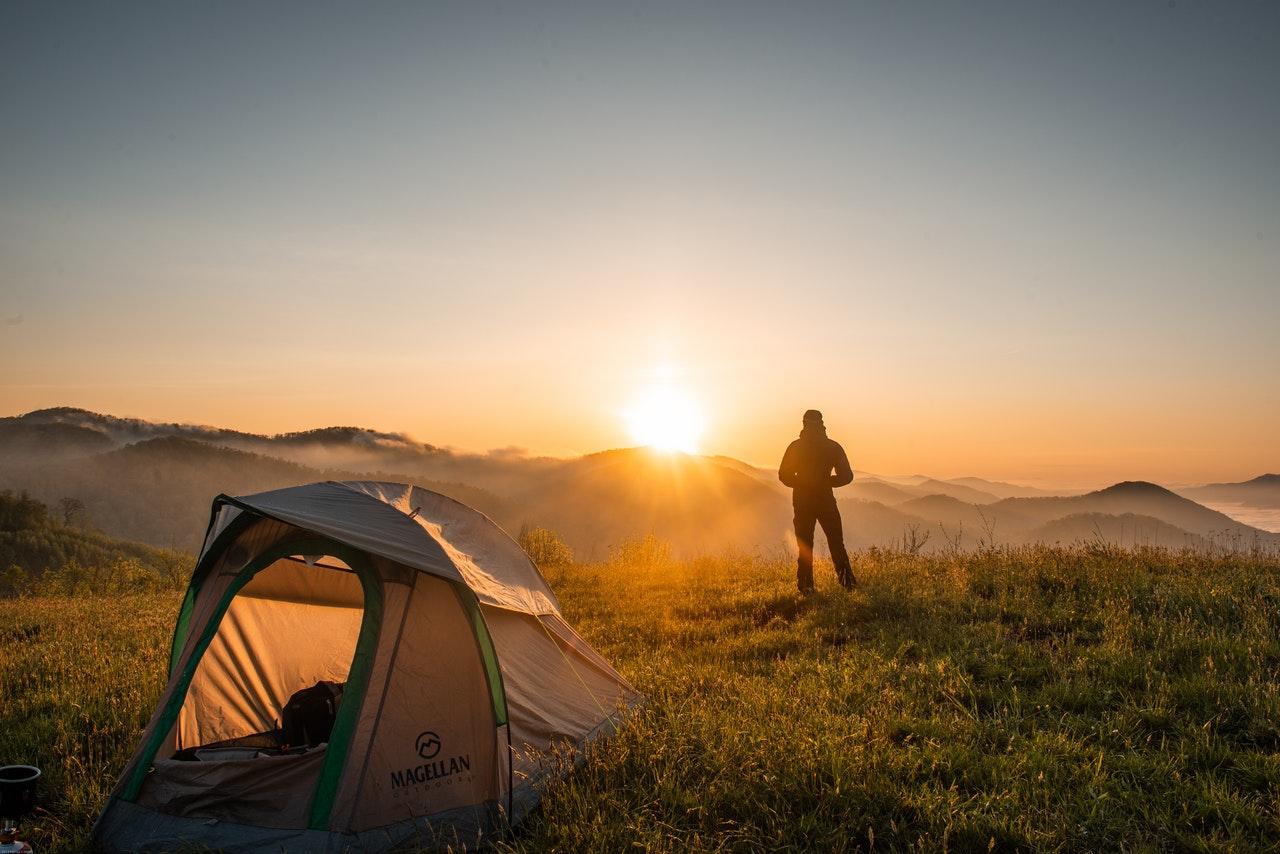 Mand er ude i naturen i telt