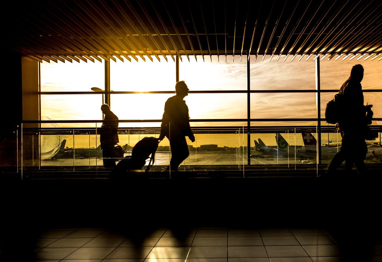 Personer går igennem lufthavn med solnedgang i baggrunden